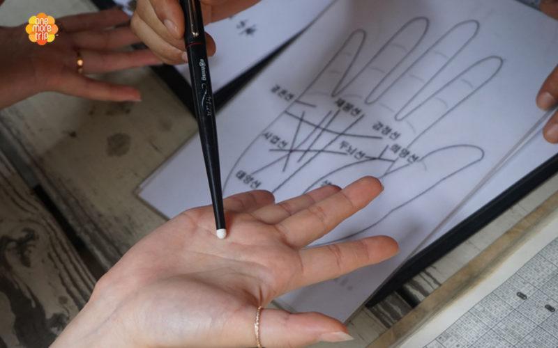 Korean fortune teller pointing at palm